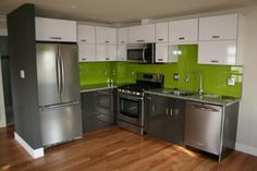 Denver CO Painting - http://www.streamlinepaintingdenver.com/denver-painting.php - This kitchen was given a makeover and now is a cool and cozy urban kitchen - highlighted with the beautiful green apple paint color along the glass covered backsplash wall. . .making it really pop!