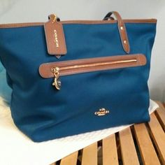 """Coach Sawyer tote. NWT Peacock Blue! This Coach purse is brand new with tags! It's a lovely Peacock blue with the perfect brown leather accents and gold metal.  12"""" x 6.5"""" bottom. 15"""" across the top. 10.5"""" height. Strap drop is 9"""".  The price is firm. Sorry, no trades. Thanks! :) Coach Bags Totes"""