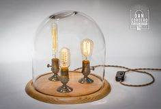 Showcased is an Extra Large version of my Edison Bell Jar Table Lamp. This lamp features 3 nostalgic style light bulbs (40 watt Edison Bulb, 40 watt Radio Bulb and 40 watt Tubular Bulb). The beautiful thick glass dome sits nicely in the groves of a lovely oak base and is accented with Antique Brass finish functional turn knob sockets. This unique lamp would make a great center piece as well as a conversation piece and would add an industrial charm to your home, office or retail space. This…
