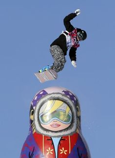 Finland's Peetu Piiroinen takes a jump near a giant matryoshka doll during snowboard slope style training at the Rosa Khutor Extreme Park ah...