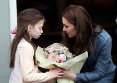 Kate receiving a flower from one of the children