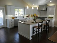 great kitchen in white with dark brown floor and plenty of light