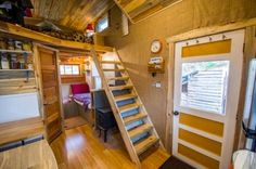 An18-feet long MitchCraft tiny house   known as the Bookworm.   It features all the golden wood colors one would expect   to find from a b...