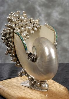 """liberty cup"". This was made in the weeks after 9/11/01. It is dedicated to all those who died . It is made of silver, polished nautilus shell, curly maple and opal. Rich's artwork 024-web by Dr.Rich Ragle"