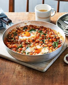 Spicy baked eggs with tomatoes and chickpeas Dr Rupy Aujla's baked eggs recipe uses fibre-rich chickpeas to keep you feeling full and is spiked with harissa paste for an extra fiery kick. It's a wonderful brunch dish for the weekend or even as a Spicy Recipes, Cooking Recipes, Healthy Chickpea Recipes, Cooking Eggs, Recipes With Chickpeas, Best Healthy Recipes, Mama Cooking, Blender Recipes, Cooking Games