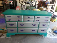 Thrift store dresser makeover - 80s style dresser got an update with bright teal satin on the main portion, silver spray paint on the drawer faces, and purple spray paint on the hardware.  Now very bright and colorful for my little girl's room.  Also, hung an old, ornate-looking mirror with same purple paint as hardware above.