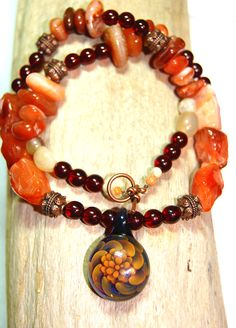 Because I love to watch the show,' Ancient Aliens' and I really love the jewelry that Giorgio Tsoukalos wears I decided to create my own version of one of his necklaces.  I used Carnelian stones and nuggets, garnet red Czech glass beads, Italian Onyx gemstone beads near the clasps, antique copper spacers and four random beads I can't really identify. Everything is strung on antique copper beading wire and the toggle clasp is also antique copper.