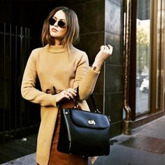 Kristina Bazan wears a mock-neck sweater, suede skirt, top-handle bag, and round sunglasses