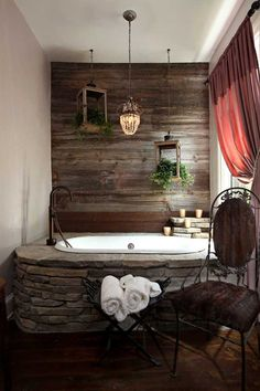 Stone encased bathtub set against wall of reclaimed wood. Also love the old lanterns turned into hanging planters.