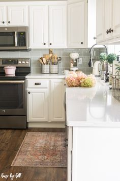 A Gray and White Kitchen with Pink Accents and Vintage Rug