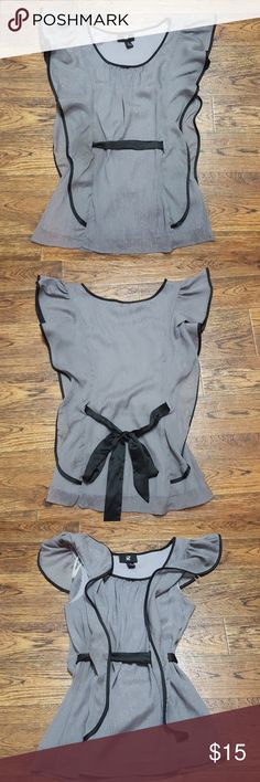 Gray Flowy Dress Shirt Top ✔Bundle your likes for a discount!  Made from 100% polyester, this dress top is sleeveless with an overlay from shoulder to waist. Shimmering gray material with black trim. Ties at waist in back. Has zero signs of wear, looks new. Iz Byer Tops Blouses