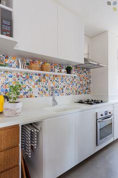A bancada - que se estende até a área de serviço - foi escolhida para compor com os armários e permitir que a parede fosse a protagonista da cozinha.