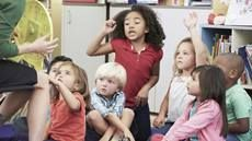 Group of young children in class responding to the teacher's question