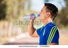 Young Latin runner drinking some water in a running track