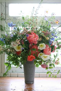 Arrangement of poppies and peonies spring in Washington state.Sweet pea vines