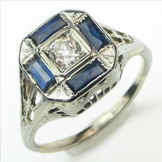 """Checkers: During the jazz age, when all things """"modern"""" were the rage, jewelry was often proudly marketed as containing """"scientific""""(aka synthetic) sapphires. This Art Deco ring is set with a quartet of those crisp blue modern marvels, surrounding a bright antique (natural) diamond. Stylized Deco arches, diagonals and flowers create the lovely shoulders and under gallery. Ca.1930. Maloys.com"""