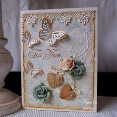 "Project details:  Cream cardstock Prima designer paper ""Delight"" Impression Obsession  die ""Heart Flourish"" (Die 126-U) JustRite sentiment stamp from the ""Victorian Nested Frames and Occasions"" stamp set Martha Stewart butterfly punches Wooden hearts Cord Pearls Prima paper roses Skwiglues glitter ""Crystal"" Lace Tim Holtz distress ink ""Tea Dye"""