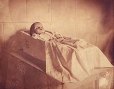 POST MORTEM (Paul Frecker collection) - A mid-twentieth century snapshot showing an infant in a white coffin lying in the snow. Description from…
