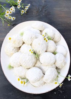 White Serving Tray of Italian Wedding Cookies Coated in Powdered Sugar on a Rustic Table