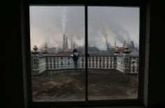 A girl reads a book on her balcony as smoke rises from chimneys at a steel plant, on a hazy day in Quzhou, Zhejiang province, China, April 3, 2014.REUTERS/Stringer