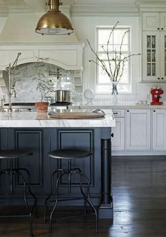 The dark blue color on the base of the kitchen island highlights the veining in the Calcutta marble top.