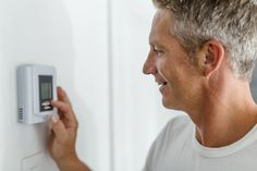 Smiling Man Adjusting Thermostat On Home Heating System. A Smiling Man Adjusting , Hvac Design, Home Heating Systems, Cheap Energy, Energy Providers, Solar Energy Projects, Duct Cleaning, Energy Conservation, Smiling Man, Saving Money