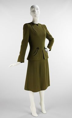 """Wool Suit 1945. In her own notes, this suit is repeatedly referenced as the """"Fencer Suit."""" Throughout her career, she repeated this silhouette, making it one of her classics. The pockets, trimmed with braid, are actually inspired by the Hussar uniforms she saw in Vienna when visiting as a child."""