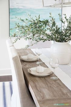 -Coastal Dining Room Refresh & Storage Solutions- A simply fall tablescape with linen chair, reclaimed wood table, white vase, olive leaf stems, and neutral striped napkins. Coastal Style, Coastal Decor, Coastal Cottage, Coastal Curtains, Coastal Farmhouse, Coastal Furniture, Modern Coastal, Cottage Living, Coastal Fall