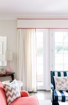 I feel like the red banding on the valance and drapes makes this simple window treatment a focal point in the room. Preppy Traditional Interior Design by Chloe Warner