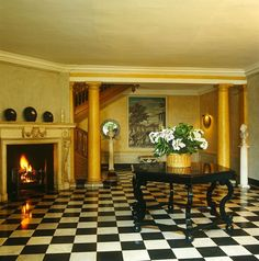 In this entrance hall an hexagonal ebony table with a simple arrangement of white hydrangeas forms an arresting focal point ~ John Stefanidis design