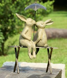 Bunny Lovers on Bench -Romantic garden sculpture of a Rabbit couple sitting on a metal bench with their legs on opposite sides while kissing under an umbrella.The cast aluminum Bunnys sculpture has been hand polished with a durable lustrous bronze patina that is suitable for outdoor applications.