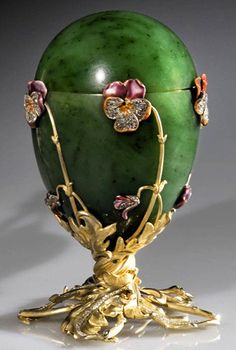 """Faberge Imperial Easter Egg, The """"Pansy Egg"""", 1899. This egg was formerly known as the """"Spinach Jade Egg"""", and is made of nephrite, gold, diamonds, and white, red, green, and opaque violet enamel. It rests on a bouquet of twisted gold leaves, from which grows five flowers and five buds of pansies, enameled in various nuances of violet and set with diamonds."""