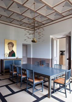 The dining room of Pierre Yovanovitch's 17th-century château in Provence boasts a fanciful Paavo Tynell lighting fixture and a portrait by Stephan Balkenhol.