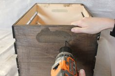 Use an electric drill to drill holes on the outside of the crate for the cabinet pulls