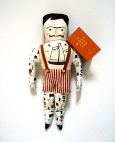 Tattooed man doll by the black apple.