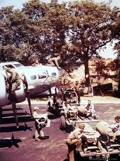 """Ground mechanics make a final check-up as ordnance men """"fin"""" 2000 lb. bombs prior to loading into a Boeing B-17 at a base in England."""