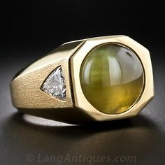A magnificent, glowing 10.00 ct. cabochon Cat's Eye Chrysoberyl of a sumptuous greenish-honey hue with a strong, shimmering eye that moves clear across the stone. The hexagonal-shape mounting is rendered in heavy 18K yellow gold with each textured side displaying a flush-set, bright-white, triangular brilliant-cut diamond for a total weight of 1.40 carats. A quite handsome, first-class trophy ring.