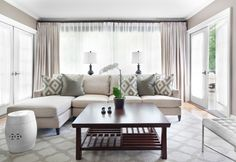 So breezy and bright! Beige couch with pale grey walls. Introduce colour on the pillows and accessories