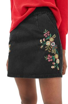 Colorful floral embroidery sweetens this black denim skirt cut to show a long length of leg.