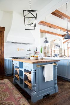 A blue center island changes aesthetic in a natural rustic way while using a set of woven pull out bins instead of drawers and displaying a brass towel bar on the end under the butcher's block counter.
