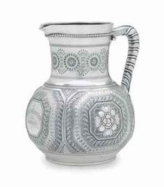 A SILVER WATER PITCHER MARK OF TIFFANY & CO., NEW YORK, 1865-1870 In the Persian taste, globular, the body finely decorated with octagonal panels enclosing large blossoms, the neck with geometric band, the handle with female mask join, engraved 'Charles O'Conner Esq./with/Gratitude' to central octagonal panel, marked under base, also marked 1511/2519 9 in. (22.8 cm.) high; 39 oz. 10 dwt. (1,234 gr.)