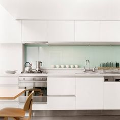 Loveliness! Smooth white cabinetry, everything recessed, glass splash back... yes please!