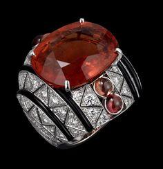 Ring Platinum, one 24.14-carat cushion-shaped brown tourmaline, cabochon-cut orange sapphires, onyx, brilliants.