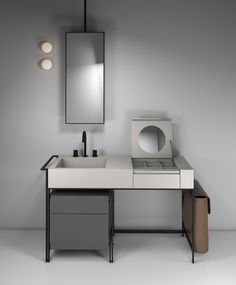 "NARCISO bathroom collection by CIELO, made up of large ceramic washbasin with a large basin and a convenient top combined with a ""vanity"" section, including mirror and compartments. All items are in the Pumice finish. The vanity is set within an elegant asymmetrical structure in matte black steel.  The drawer unit is in the Cemento finish and the laundry bag on the side is in natural leather. Argo is the ceiling-mounted mirror. Design by Parisio and Pezzano  #ceramic #bathroomdesign"