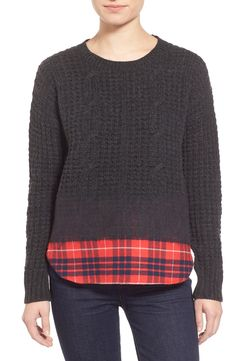A seamless hybrid of two cool-weather essentials, this cable-knit merino-wool sweater seems to dissolve into a cotton shirttail as vibrant plaid peeks out from the bottom of the distinctive style.
