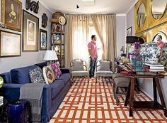 Sobre o tapete de lã da Botteh, sofá da Ateliê de Cortina feito com tecido da Donatelli, também presente nas almofadas. No alto da parede, coleção de máscaras trazidas da África. Do lado oposto, espelhos dourados da 6F Decorações