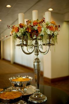 A table with appetizers was decorated with a large silver candelabra with cream pillar candles surrounded by mounds of the wedding flowers. | by Dorothy McDaniel's Flower Market; Spindle Photography