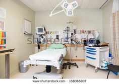 Interior of emergency hospital room with bed and equipment - stock photo