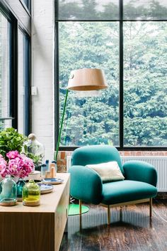 living room with turquoise chair and a green view