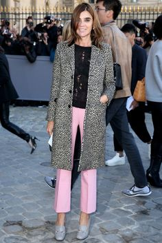 Carine Roitfeld wears pink pants with a black sweater and printed coat. She pairs the look with Dior heels.